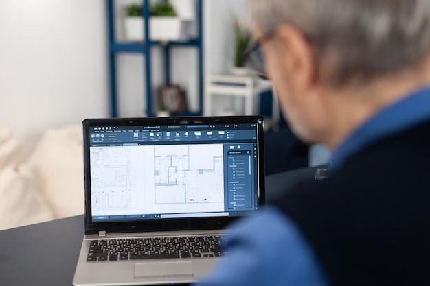 프로젝트를 완료하기 위해 노트북 작업을 하는 수석 건축가의 오버숄더 샷. 숙련된 건설 엔지니어 디자이너가 홈 오피스에서 노트북 컴퓨터로 집 청사진을 보고 있습니다.