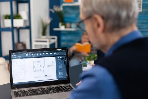 노트북 작업을 하는 수석 건축가의 어깨 너머로 촬영