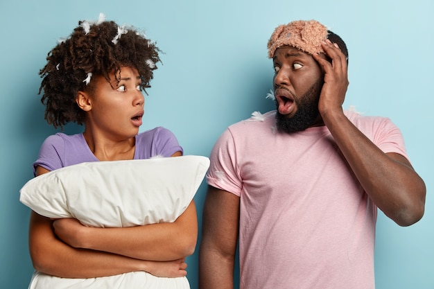 Oversleeping concept. frightened afro couple missed ringing alarm clock, react in horror at time, hold white pillow, wear sleepmask, look in horror at each other, isolated over blue wall