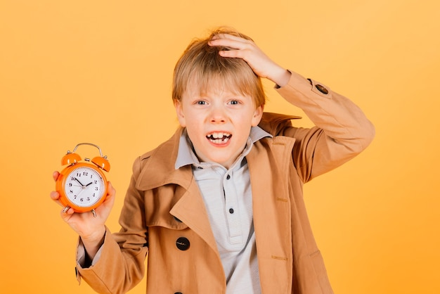 Overslept. worried awake teen boy with alarm clock is shocked because it is too late