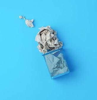 しわくちゃの紙で転倒した青い金属バスケット