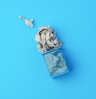 Overturned blue metal basket with crumpled pieces of paper