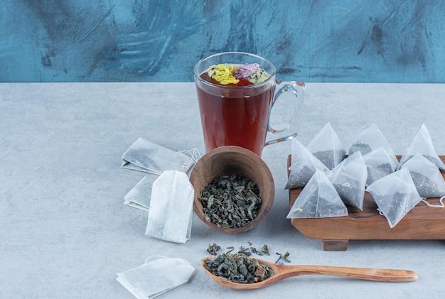 Ciotola capovolta piena di foglie di tè, cucchiaio, una tazza di tè e bustine di tè a bordo su marmo.