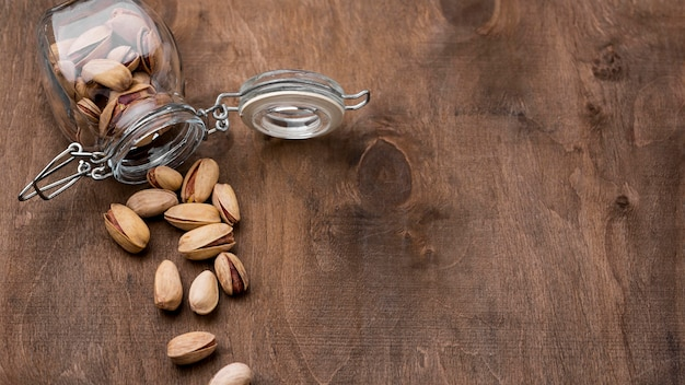 Overturned glass jar with roasted pistachio nuts copy space