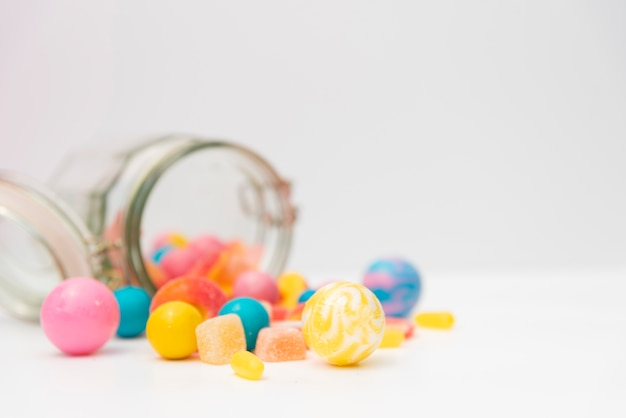 Overturned jar with delicious candies on table