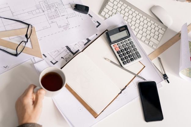 Overview of hand of engineer with cup of black tea or coffee by desk during work over calculations for sketch or project
