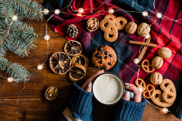 Overview of hands of female in knitted sweater holding mug with hot drink surrounded by traditional xmas food and symbols