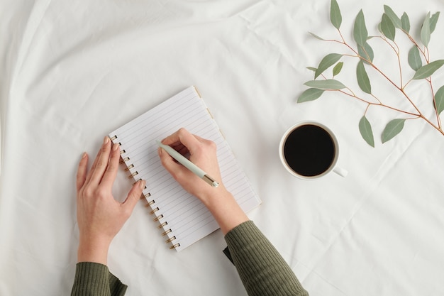 Overview of hands of young businesswoman with pen making notes in notebook while having cup of coffee