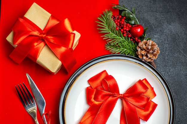 Overview of new year background with red ribbon on dinner plate cutlery set decoration accessories fir branches next to a gift on a red napkin