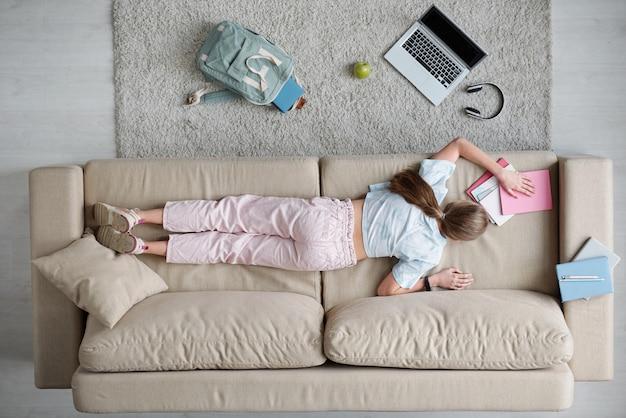 Обзор спины девочки-подростка, лежащей на диване в окружении рюкзака, ноутбука, наушников и тетрадей во время выполнения домашнего задания