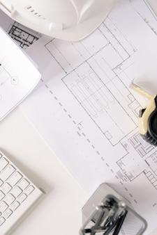책상 위의 건축가 작업을위한 엔지니어링 스케치 및 기타 소모품이 포함 된 청사진 개요