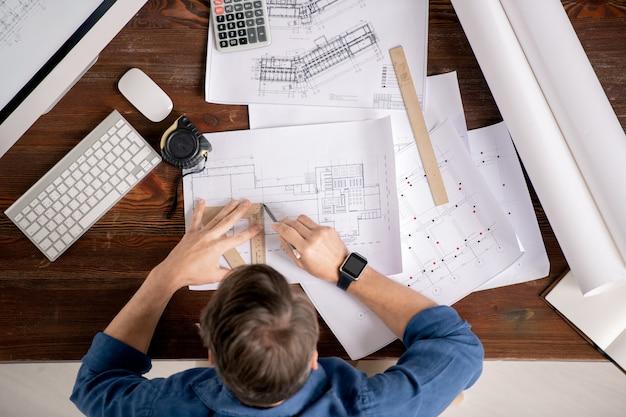 Обзор занятого инженера с линейкой и карандашом, сидящего за столом и рисующего линию на эскизе архитектурного сооружения