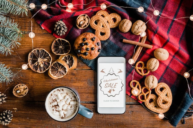 Обзор домашней страницы рождественской распродажи интернет-магазина в смартфоне в окружении горячих напитков, сладостей и грецких орехов
