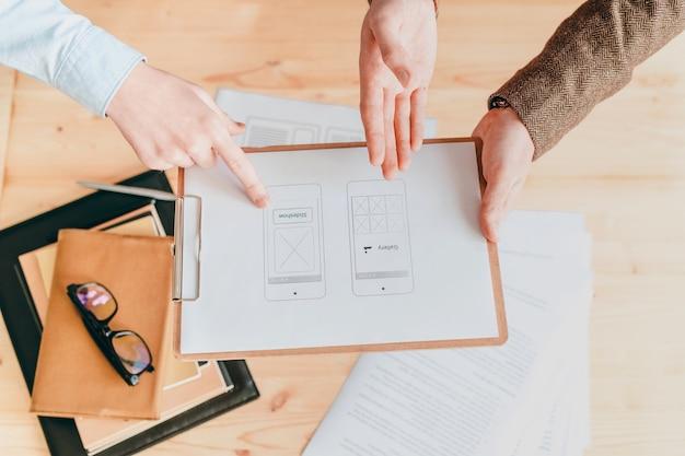 두 명의 현대 웹 디자이너가 논의하는 종이에 인터페이스 또는 프로그램 응용 프로그램이있는 클립 보드 개요