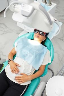충치 예방 개요 치과 시술 중 치과 의자에 앉아있는 여성 아름 다운여자가 미소를 닫습니다. 건강한 미소. 아름다운 여성 미소.
