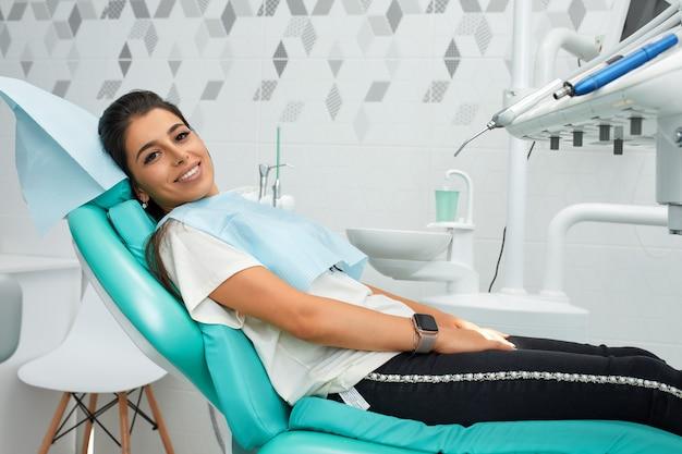 虫歯予防の概要歯科治療中の歯科医の椅子にいる女性美しい女性の笑顔がクローズアップ。健康的な笑顔。美しい女性の笑顔。