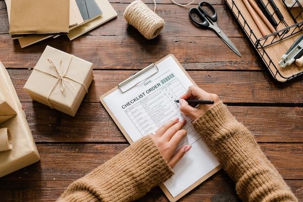 체크리스트에 주문 된 항목 반대 진드기를 넣는 동안 형광펜을 들고 나무 테이블 위에 여성 손의 개요
