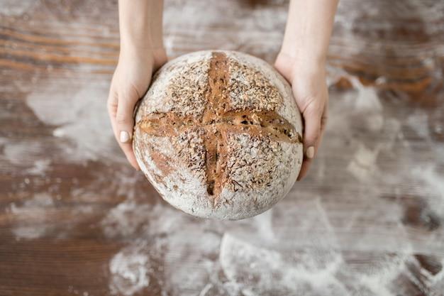 테이블과 밀가루 위에 여성의 손으로 잡은 신선한 호밀 홈 메이드 라운드 빵 개요
