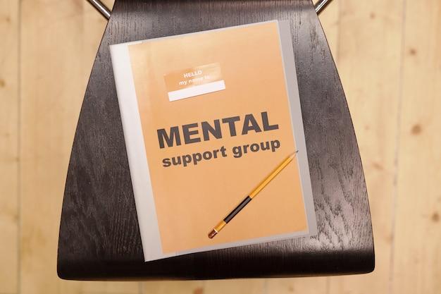 Обзор серой папки с надписью «группа психологической поддержки» и карандашом, лежащим на черном деревянном стуле перед камерой