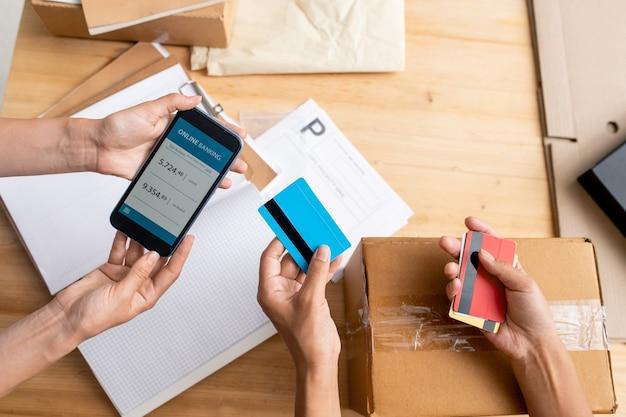 Обзор рук двух менеджеров-женщин, которые держат смартфон с оператором онлайн-банкинга и пластиковыми картами над рабочим местом