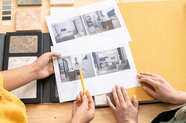 モダンなアパートの写真を議論するインテリアの2人の若い女性デザイナーの手の概要