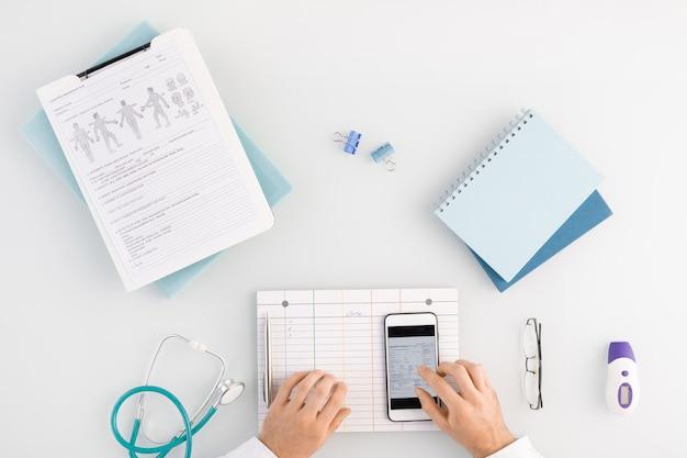 職場でスマートフォンのデータをスクロールしながら、医療従事者が空白のカードとガジェットのタッチスクリーンを手にした概要
