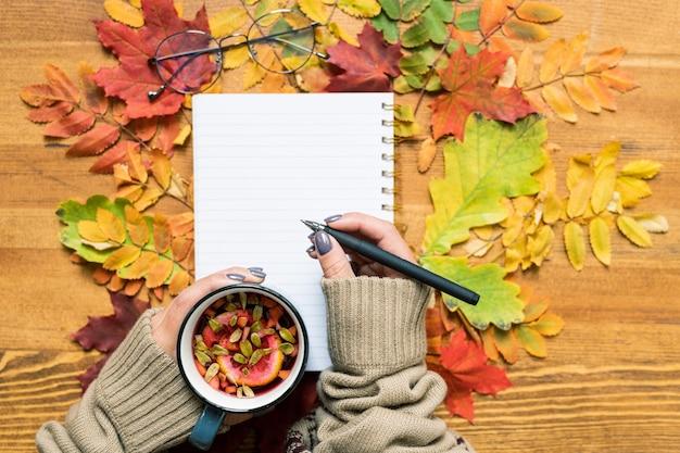 Обзор рук ученика, держащего горячий травяной чай и ручку над открытой тетрадью или блокнотом