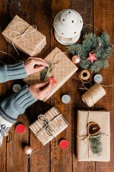 Обзор рук молодой женщины, завязывающей узел на упакованной и обернутой подарочной коробке во время подготовки подарков к рождеству