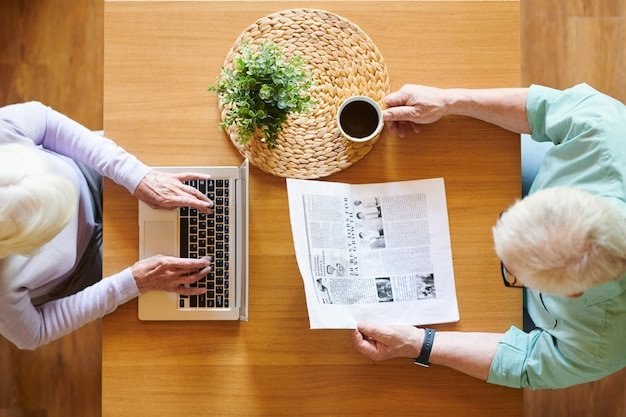 Overview of senior husband with newspaper and wife with laptop sitting by wooden table in front of one another