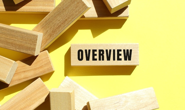Overview text written on a wooden blocks on a yellow background