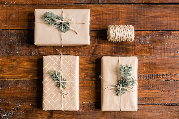 Overview of three packed, wrapped and bound giftboxes with conifer on top and spool of threads on wooden table