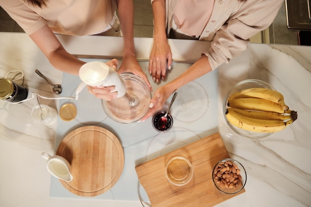 Overview of two contemporary females standing by kitchen table and mixing up ingredients of homemade icecream with electric mixer
