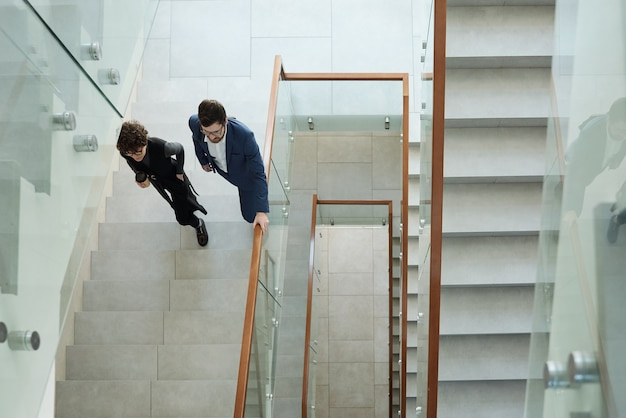 Overview of two young business people in formalwear walking upstairs inside contemporary office building