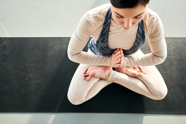 Overview of young serene female keeping balance while sitting on mat in one of yoga poses during training in gym or leisure center