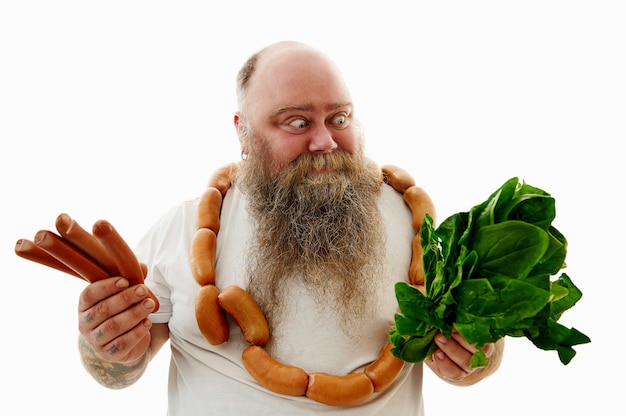 An overweigh man with a bunch of sausages around the neck looking at spinach and holding sausages on the other hand try to choose what is more healthy