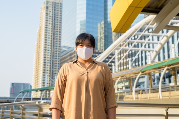 Overweight asian woman with mask at skywalk bridge against view of the city