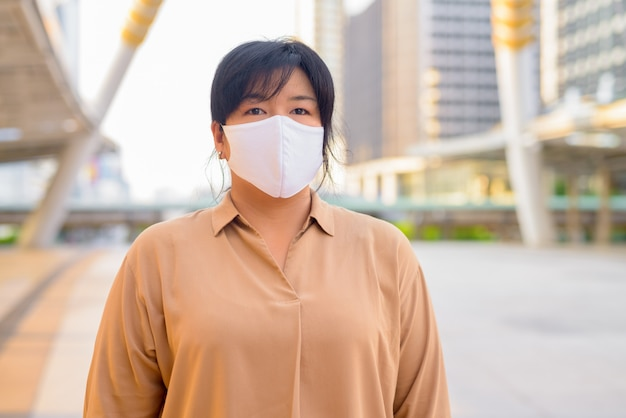 Overweight asian woman with mask at skywalk bridge