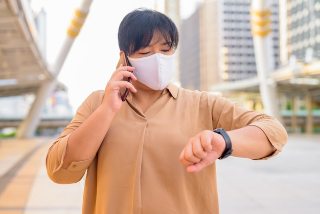 Overweight asian woman with mask talking on the phone and checking time at skywalk bridge