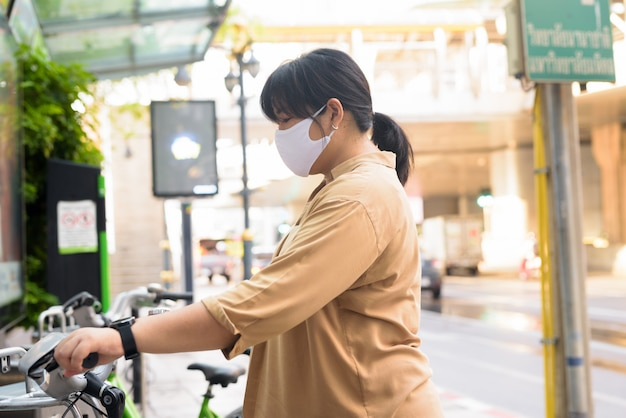 Overweight asian woman with mask using public bicycle rental ...