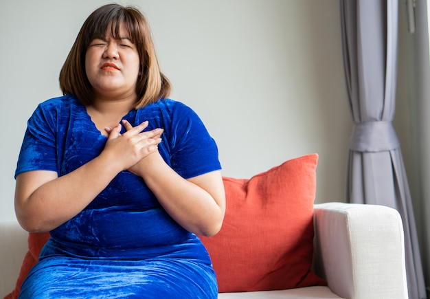 Overweight asian women are sitting on the sofa in the living room.