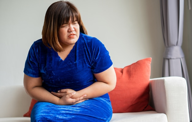 Overweight asian women sitting on the sofa in the living room.