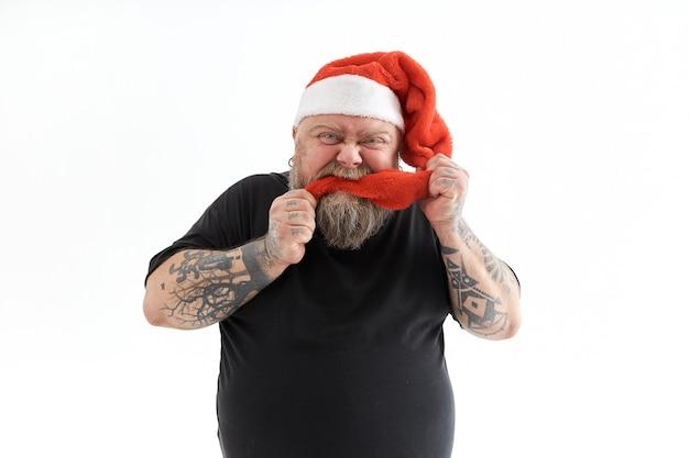 과체중 수염 난된 남자 웃고 크리스마스 모자를 쓰고
