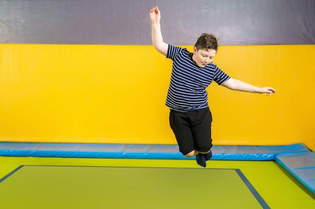 아이들을위한 스포츠 센터에서 실내 트램폴린에서 점프 과체중 귀여운 소년