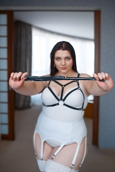 Overweight depraved woman in erotic lingerie holding leather whip.