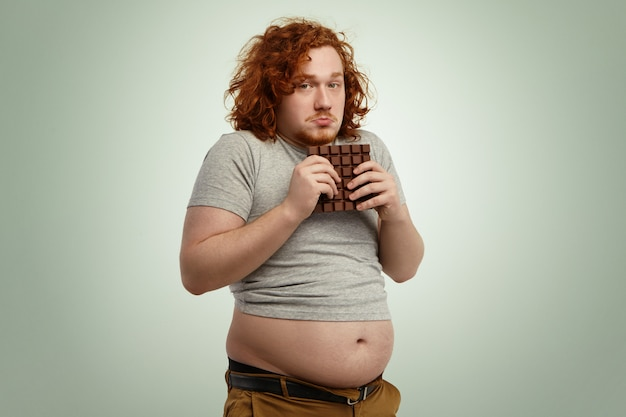 Overweight fat man with ginger curly hair looking indecisive and hesitant, holding large bar of chocolate with both hands while forbidden to eat sugar, and junk food because of strict low-carb diet