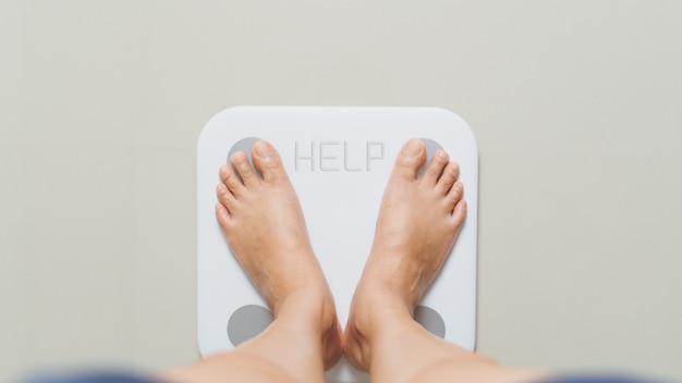 太りすぎの女性がヘルプワードで自宅の白い体重計に立っています。