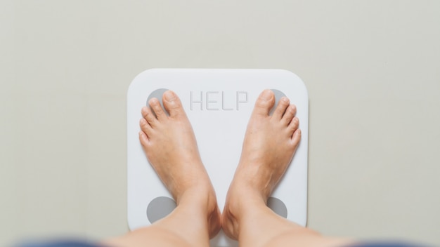 Overweight female is standing on white scales at home with help word
