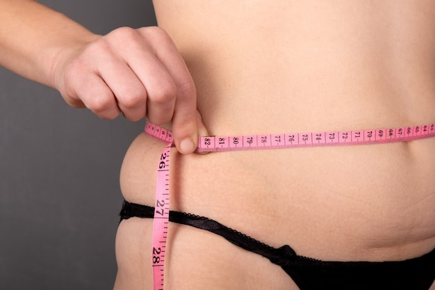 Overweight, a girl measures her waist with a centimeter.