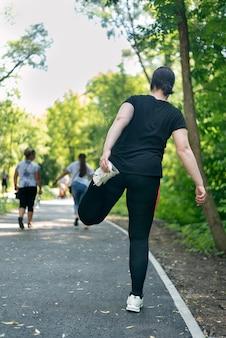 Девушка с избыточным весом занимается спортом в парке. молодая женщина большого размера делает разминку перед бегом.