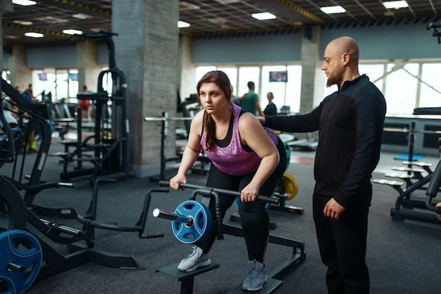 Overweight girl with trainer doing exercise in sport club, fitness training with instructor
